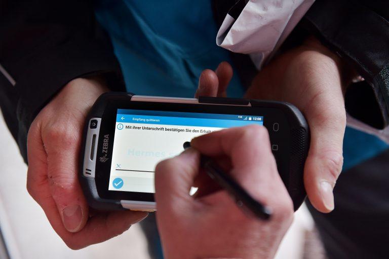 Kunde bestätigt den Empfang eines Pakets auf der neuen Scannergeneration von Hermeszusteller scanner handscanner unterschrift