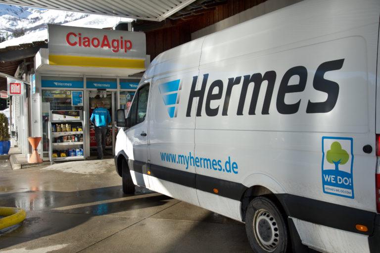 Zusteller auf seiner Tour an einem Hermes PaketShop (Foto: Hermes)zustellung transporter pakettransporter paketshop tankstelle schnee winter zustelltour tour