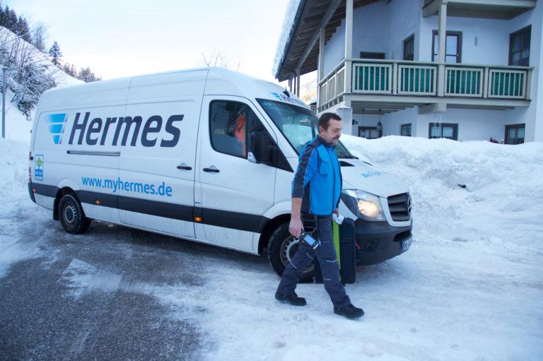 Ein Zusteller liefert ein Gepäckstück an die Haustür (Foto: Hermes).zusteller zustellung gepäckversand winter schnee haustür haustürzustellung gepäck