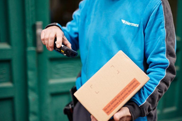 Ein Hermes Zusteller scannt ein Paket. (Foto: Hermes/Willing-Holtz)  Päckchen; Sendung; Scanner; Paket; scannen; Haustür; Zusteller; Bote; Technologie