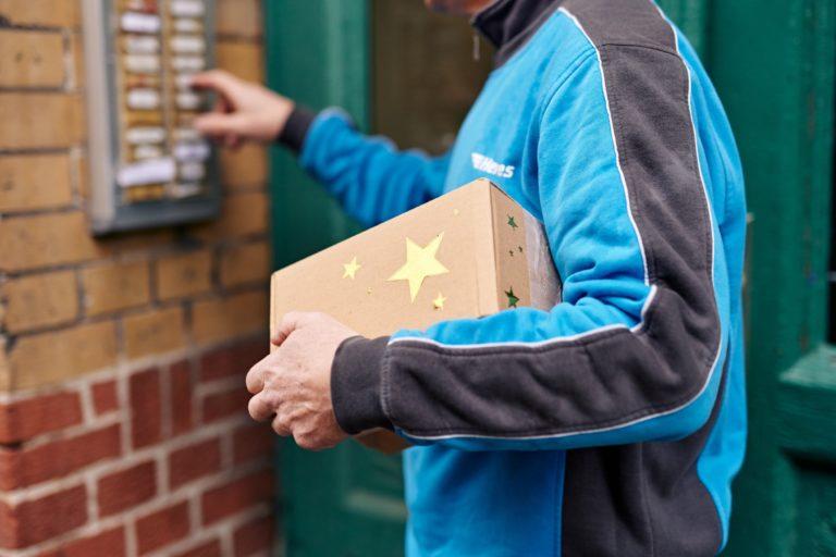 Hermes Zusteller mit einem Weihnachtspaket. (Foto: Hermes/Willing-Holtz)  Zusteller; Paket; Bote; Haustür; Päckchen; Weihnachten; Klingel; Zustellung; Sendung
