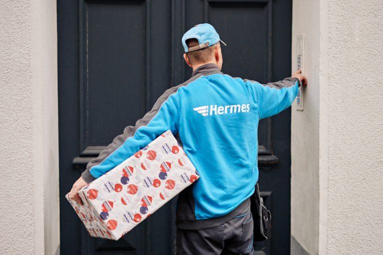 Hermes Zusteller mit einem Weihnachtspaket. (Foto: Hermes/Willing-Holtz)  Paket; Zustellung; Zusteller; Bote; Paketbote; Haustürzustellung; Haustür; Klingel