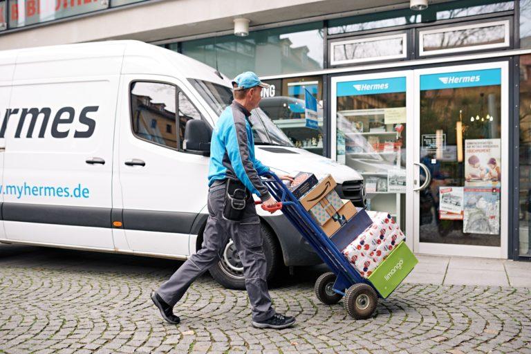Hermes Paketzusteller beliefert einen PaketShop. (Foto: Hermes/Willing-Holtz)  PaketShop; Zusteller; Bote; Lieferung; Pakete; Weihnachten; Zustellung; Shop