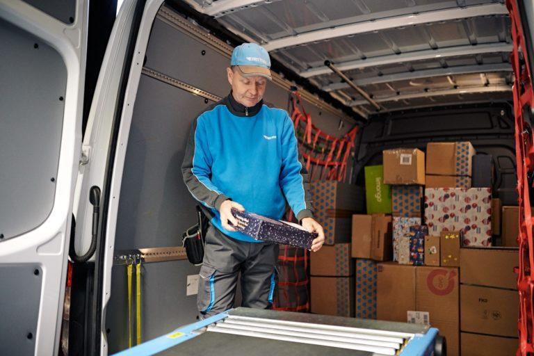 Ein Hermes-Zusteller lädt Pakete in sein Fahrzeug. (Foto: Hermes/Willing-Holtz)  Pakete; Zusteller; Paketbote; Bote; Päckchen; Beladung; Transporter; Fahrzeug; Sortierung; Weihnachten