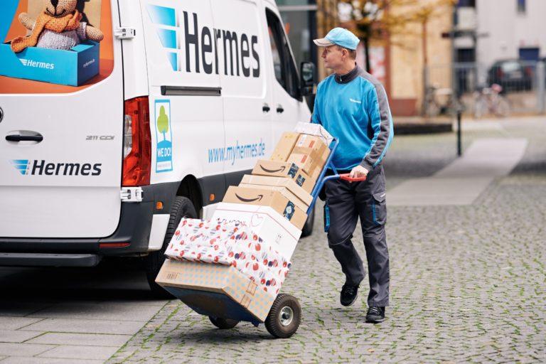 Ein Hermes Zusteller mit Paketen vor seinem Fahrzeug. (Foto: Hermes/Willing-Holtz)  Zusteller; Bote; Paket; Pakete; Päckchen, Weihnachten; Paketzustellung; Sendung; Fahrzeug, Trasporter, Sprinter