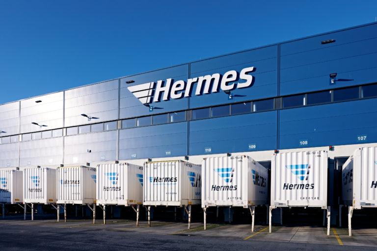 Außenaufnahme des Hermes Logistik-Centers in Mainz (Foto: Hermes/Willing-Holtz)  Logo; Logistikzentrum; Schriftzug; Makenzeichen; Container; Hof; Wechselaufbaubrücken; Tore; Beladetore