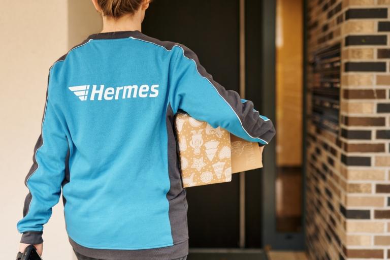 Hermes Mitarbeiterin mit weihnachtlich verpackten Paketen (Foto: Hermes/Willing-Holtz)  Weihnachten; Peak; Geschenk; Geschenkpapier; Präsent; Paket; Päckchen; Zustellung; Bote; Paketzusteller; Lieferant; Karton; Sendung; Lieferung
