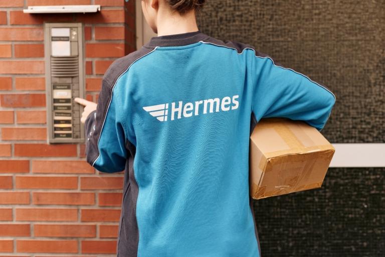 Hermes Mitarbeiterin an einer Haustür (Foto: Hermes/Willing-Holtz)  Paket; Päckchen; Zustellung; Bote; Paketzusteller; Lieferant; Karton; Sendung; Lieferung; Haustür