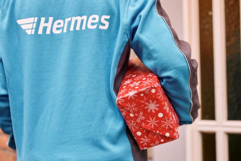 Hermes Mitarbeiterin trägt ein Paket (Foto: Hermes/Willing-Holtz)    Paket; Päckchen; Zustellung; Bote; Paketzusteller; Lieferant; Karton; Sendung; Lieferung; Haustür; Scanner; Technologie