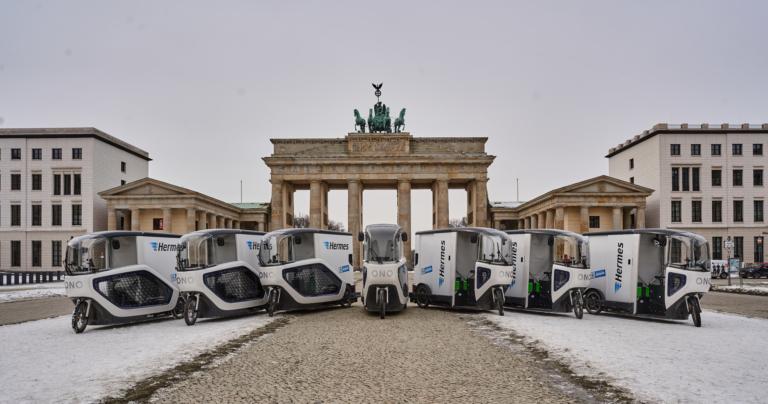 Sieben Hermes Cargo-Bikes der Marke ONOMOTION vor dem Brandenburger Tor (Foto: Hermes)    Berlin; emissionsfrei; Nachhaltigkeit; Zustellung; ONO