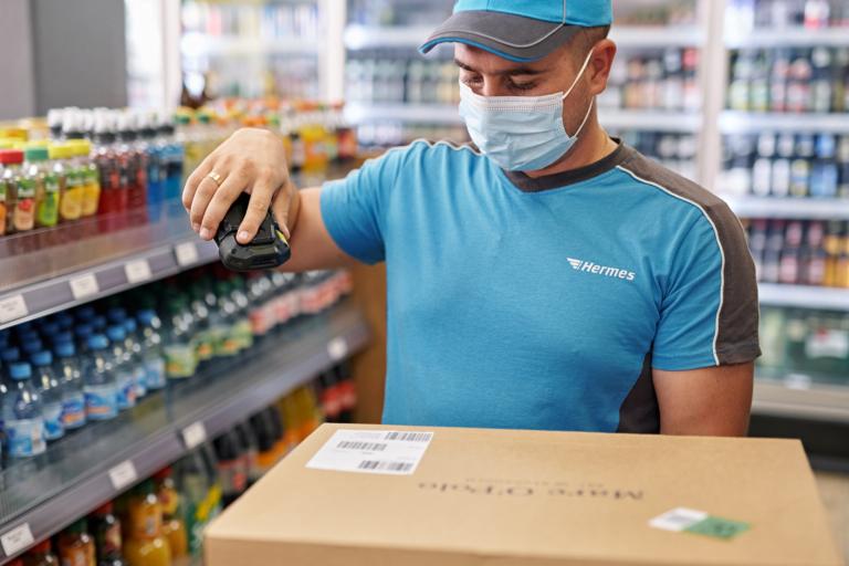 Hermes-Zusteller scannt Sendung in Berliner PaketShop (Foto: Hermes/Willing-Holtz)  PaketShop; Green Delivery Berlin; Zustellung; Zusteller