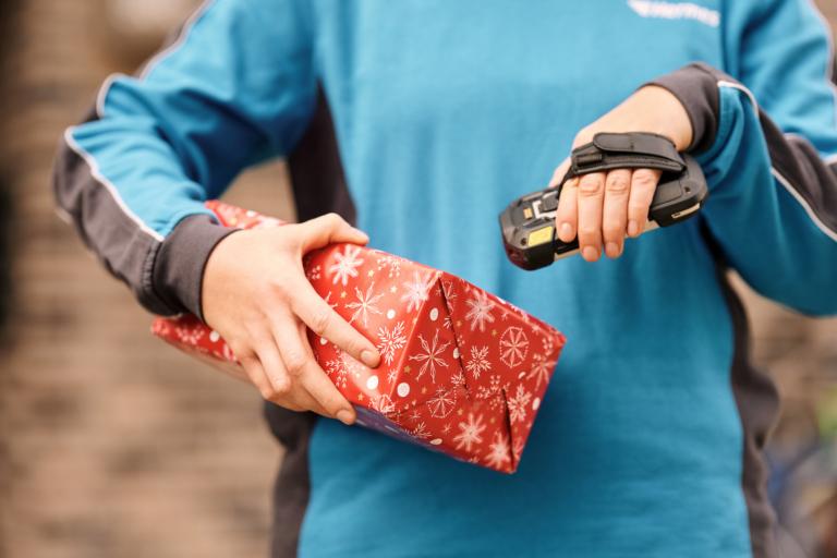 Zustellerin scannt ein privates Weihnachtspaket (Foto: Hermes/Willing-Holtz)  Weihnachten; Zustellung; Zustellerin; Scanner; Handscanner; Weihnachtspaket